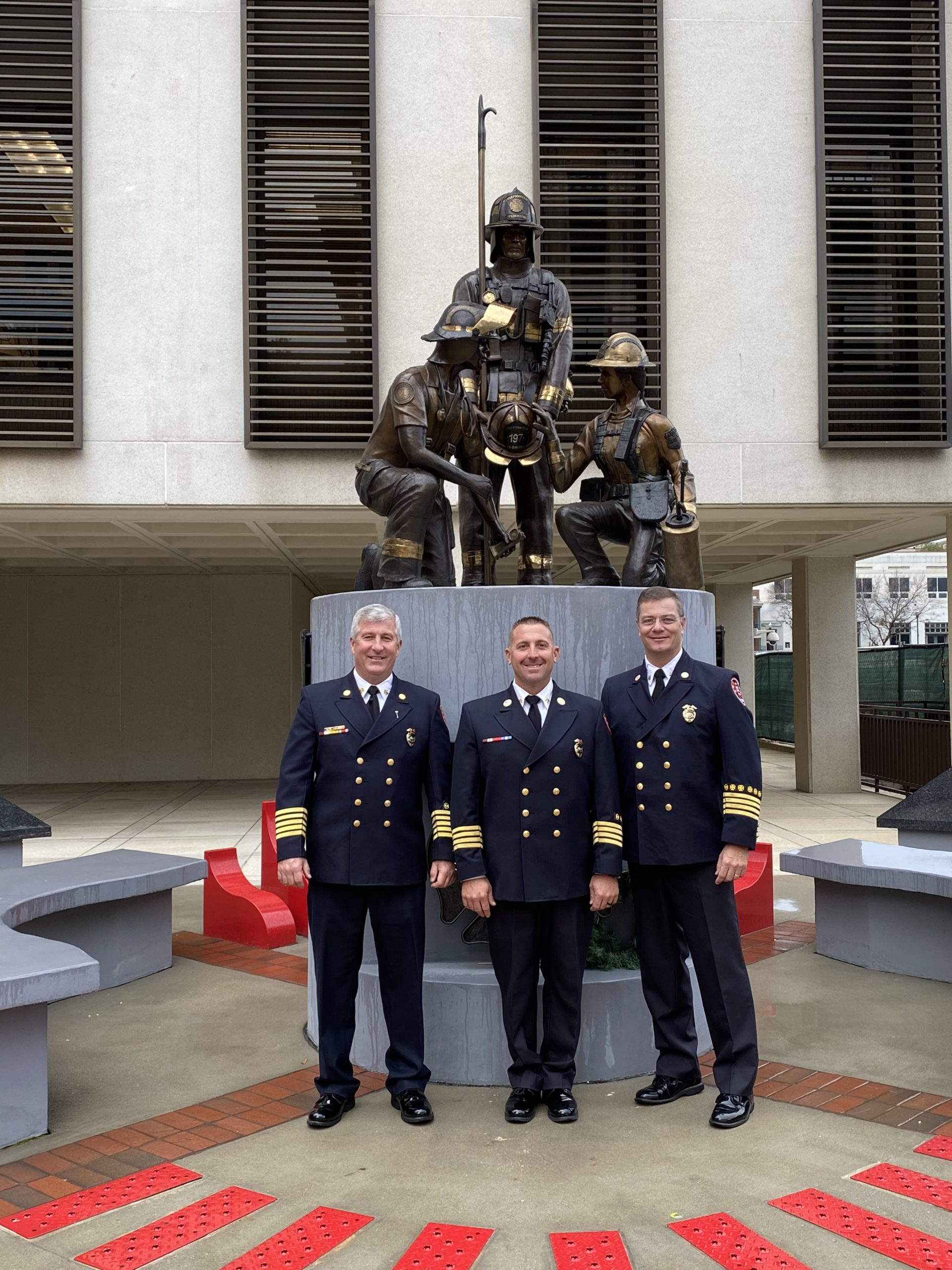 Chief Hoyle, Deputy Chief Falcone, and Deputy Chief Bradshaw photographed in front of the firefighter memorial statue at the capital in Tallahassee, FL.